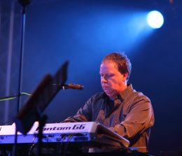 "John Comish joined Moonshot in 2005. Previously he had been playing keyboards with progressive rock band Motor Home Madness, who released one single, ""More Tea Vicar""."